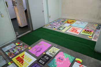 Posters hung on the floor rather than the walls of the gallery space at Common Center