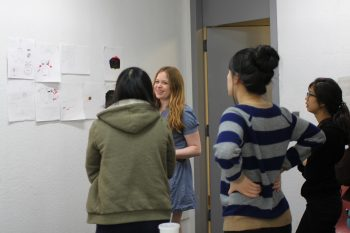 Kim Dulaney critiquing student designs mid-workshop