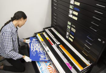 MFA student Christina Huang sorting posters in the archive.