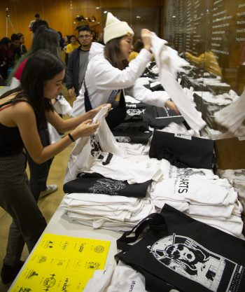 Tiana Li and Oona Lei quickly sort through shirts to fill waiting orders. Photo by Michael Worthington.