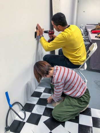 Yuchen Liu and Aren install faux tile and wall pegboard.