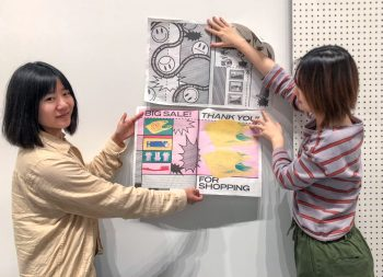 Fanyi Yu and Yuchen demonstrate how the wall will be plastered with newspapers.
